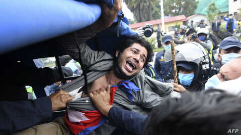 A demonstrator shouts slogans after he was detained by the police during a protest against India's newly inaugurated link road to the Chinese border, in Kathmandu, Nepal.