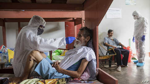 COVID-19 patients are assisted by medical staff in protective equipment at the regional hospital in Iquitos, the largest city in the Peruvian Amazon, May 9, 2020.