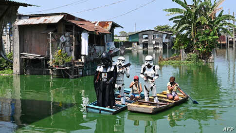 Local youth representatives dressed as Stormtroopers and Darth Vader from the Star Wars film patrol in a wooden boat around a submerged village to remind residents to stay at home during the community quarantine in suburban Manila, Philippines.