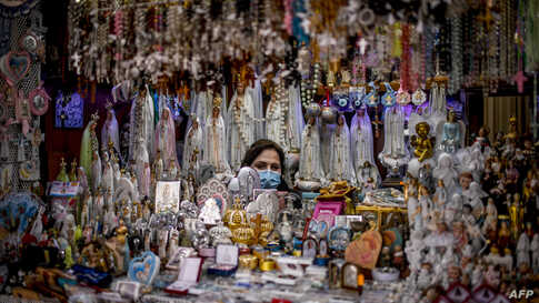 A seller of religious figurines waits for customers at her stall wearing a face mask during the 103rd anniversary of the apparitions of Our Lady of Fatima at the Fatima shrine in central Portugal.