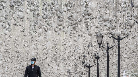 A man wearing a face mask walks along a street decorated with illuminations in central Moscow during a strict lockdown in Russia to stop the spread of the COVID-19.