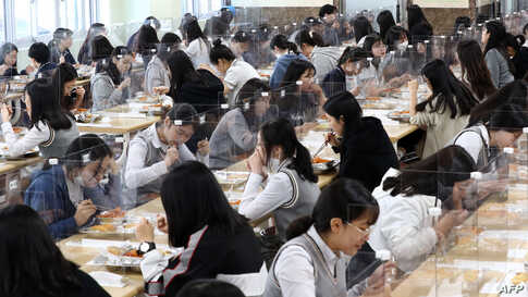 Students eat lunch at tables with protective barriers as a preventative measure against the COVID-19 at a high school in Daejeon, South Korea.