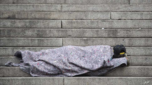 A homeless person sleeps outside the Cathedral in Sao Paulo, Brazil.