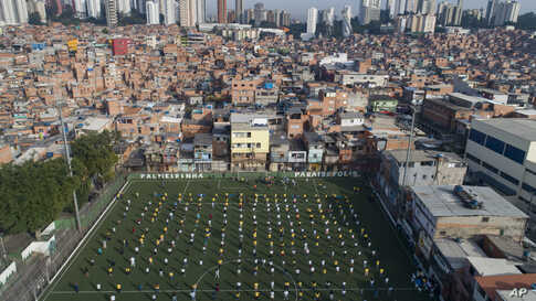 Residents of the Paraisopolis slum attend a ceremony on a soccer field in Sao Paulo, Brazil.