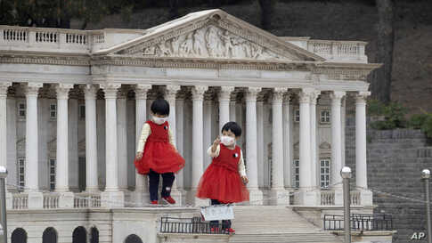 Children wearing face masks stand on the steps of a scaled replica of the United States Capitol Building at the World Park in Beijing, China.