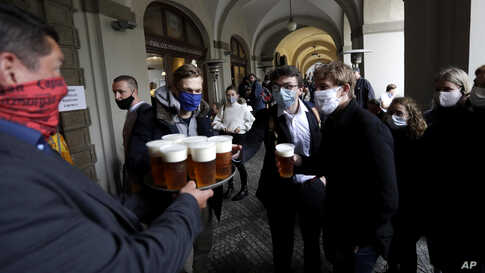 People line up for a beer at a restaurant terrace in Prague, Czech Republic, Monday, May 11, 2020. Bars, restaurants, cafes…