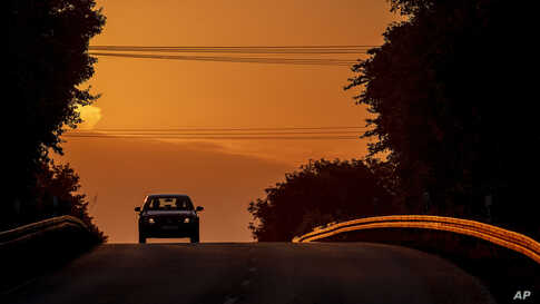 A car drives along a road as the sun rises in Frankfurt, Germany.