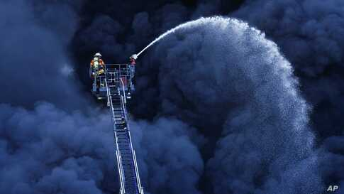 Firefighters extinguish a fire at a plastic factory in Ladenburg, Germany.