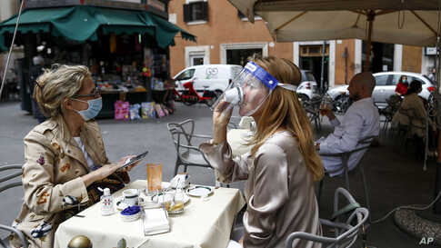 A woman sips her coffee at a cafe in Rome, Italy.Italy is slowly lifting restrictions after a two-month coronavirus lockdown.
