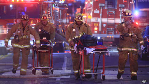 Los Angeles Fire Department firefighters push ambulance stretchers at the scene of a structure fire that injured multiple firefighters, according to a fire department spokesman, May 16, 2020, in Los Angeles, California.