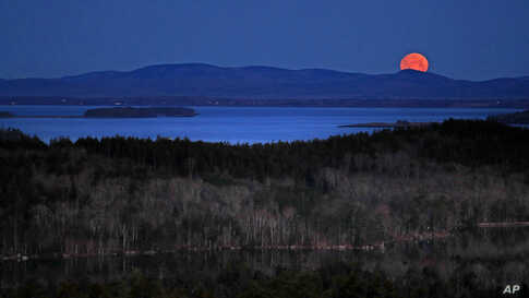 The nearly-full moon sets at dawn behind the Camden Hills in this view looking west across Penobscot Bay, near Camden, Maine.