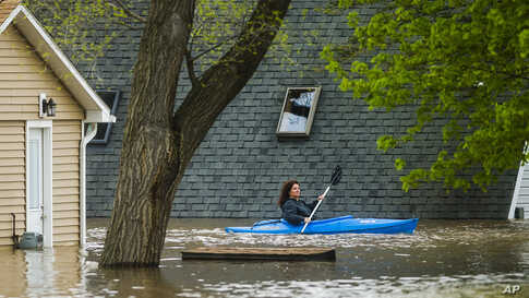 A woman use a kayak to assess the damage at homes in her neighborhood on Oakridge Road on Wixom Lake in Beaverton, Michigan. Rapidly rising water has overtaken dams and forced the evacuation of about 10,000 people from flooded communities.