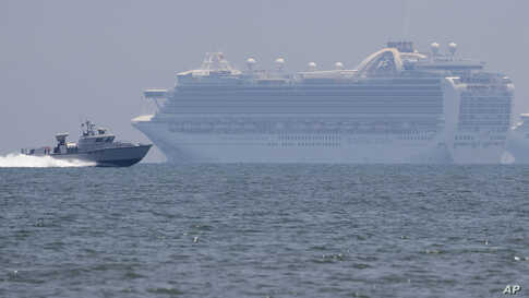 A Philippine military boat passes by the cruise ship Ruby Princess in Manila Bay.