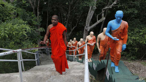 A Buddhist monk climbs the steps past statues at a deserted temple in Colombo, Sri Lanka.