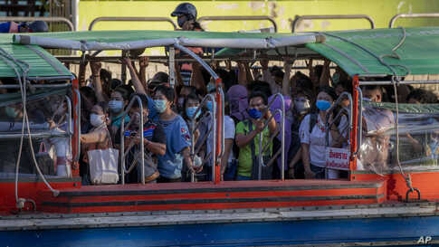 Passengers wearing face masks ride a canal boat during the evening rush hour in Bangkok, Thailand.