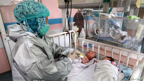 A nurse attends to newborn children who lost their mothers in an attack at a hospital, in Kabul, Afghanistan.
