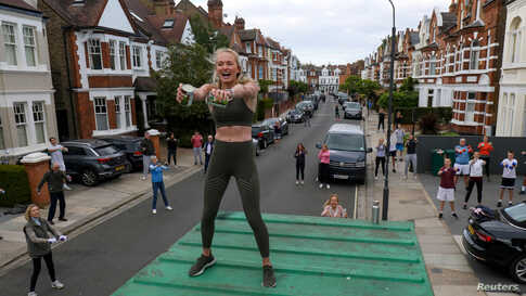 Personal trainer Flo Dowler leads the residents of Napier Avenue in a workout in Fulham, West London, May 11, 2020.