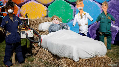 Scarecrows dressed as doctors and a patient are seen in front of rainbow colored hay bales on a farm in Billinge in Billinge, Britain.