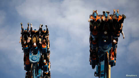 People wearing face masks enjoy a fun ride in the Happy Valley amusement park in Beijing, China.