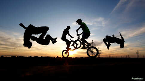 Youths wearing protective face masks use bicycles and perform a somersault as they practice parkour, during the holy month of Ramadan in the holy city of Najaf, Iraq, May 3, 2020.