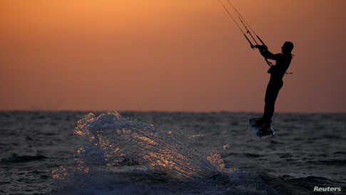 A man surfs with his kitesurfing board in the Mediterranean sea in Ashkelon as restrictions following the coronavirus disease (COVID-19) ease around Israel, May 11, 2020.