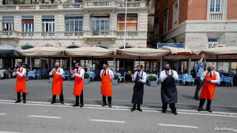 Workers applaud to thank health workers for their battle against the coronavirus disease (COVID-19) before their restaurants' reopening on the waterfront in Naples, as Italy eases some of the lockdown measures put in place during the COVID-19 pandemic.