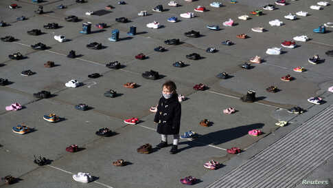 A child is surrounded by shoes, after Civil disobedience group Extinction Rebellion laid out 1,500 pairs of children's shoes in Trafalgar Square in central London to demand that government adopts a climate-friendly economic recovery plan.