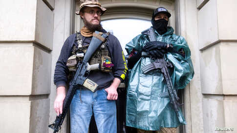 Protesters with long guns shelter from the heavy rain during a protest against Governor Gretchen Whitmer's extended stay-at-home orders to slow the spread of the coronavirus disease (COVID-19), at the Capitol building in Lansing, Michigan.