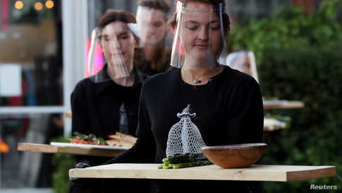 """Servers in protective gear carry food at a restaurant which is testing servers providing drinks and food to models pretending to be clients in a safe """"quarantine greenhouses"""" in Amsterdam, Netherlands, May 5, 2020."""