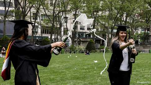 Molloy College Nursing School graduates Taylor Laufer and Yuliya Dubyna make a toast in Bryant Park, during the COVID-19 pandemic in New York, City, May 18, 2020.