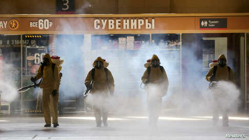 Russia's Emergencies Ministry members wearing personal protective equipment spray disinfectant near a gift kiosk at the Kievsky Railway Station amid the outbreak of the COVID-19 in Moscow. (Credit: Sandurskaya/Moscow News Agency/Handout)