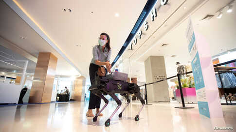 "A woman uses hand sanitizer gel from a four-legged dog robot called ""K9"" at the Central World department store, after the Thai government eased isolation measures to prevent the spread of the COVID-19 in Bangkok, Thailand."