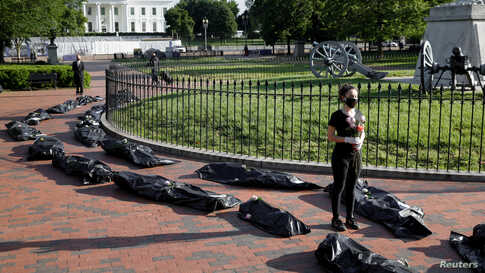 Margot Bloch stands in a line of mock body bags while holding flowers during a funeral procession demonstration for the COVID-19 victims outside of the White House in Washington, May 20, 2020.