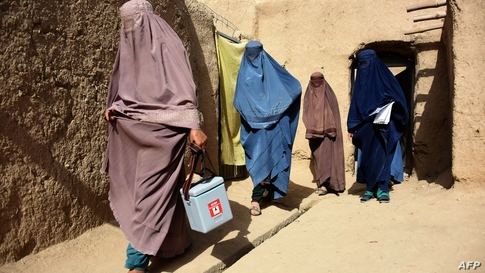 Afghan women wearing burqas from a polio immunisation team walk together during a vaccination campaign in Kandahar on October…