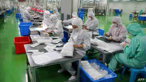 This photo taken on February 13, 2020 shows workers producing protective suits at a factory in Binzhou in China's eastern…