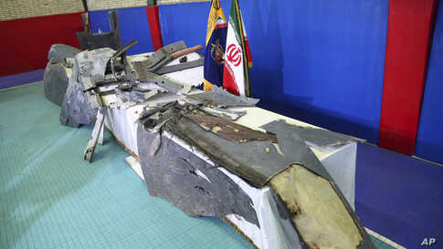 Debris from what Iran's Revolutionary Guard aerospace division describes as the U.S. drone which was shot down on Thursday is displayed in Tehran, Iran, Friday, June 21, 2019. Major airlines from around the world on Friday began rerouting their…
