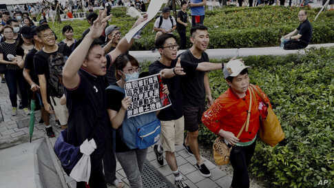 """Protesters walk behind a mainland Chinese tourists, holding a card with their demands including """"Withdrawal of extradition bill"""" and """"Real elections"""" during a march in Hong Kong, July 7, 2019."""