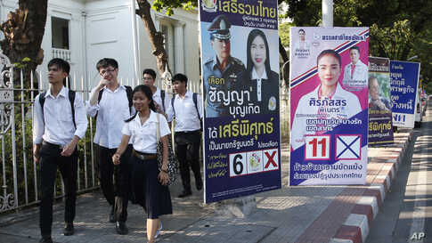 In this Tuesday, March 12, 2019, photo, students of Chulalongkorn University walks past election campaign posters in Bangkok,…