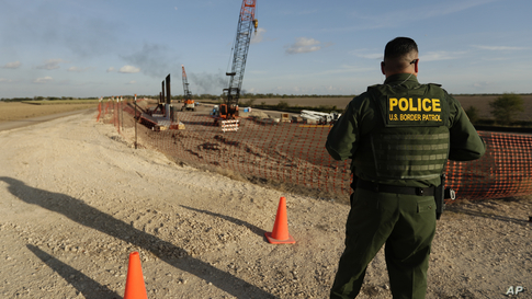 A U.S. Border Patrol agent stands over a construction site for a new section of levee border wall along the U.S.-Mexico border,…
