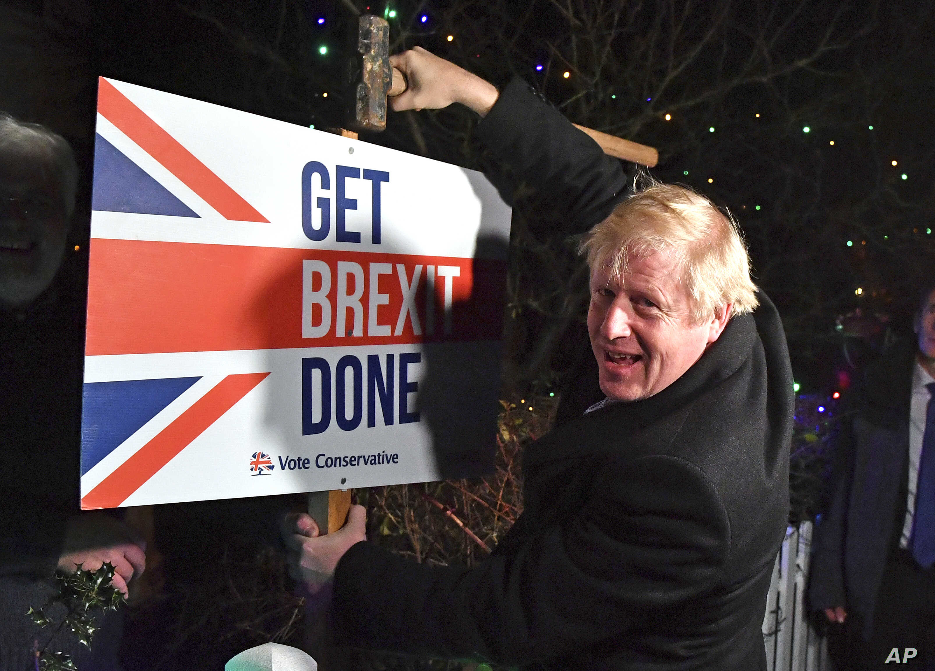 """Britain's Prime Minister and Conservative party leader Boris Johnson poses as he hammers a """"Get Brexit Done"""" sign into the…"""