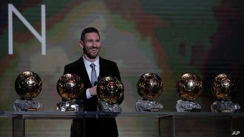 Barcelona's soccer player Lionel Messi poses with his six golden balls during the Golden Ball award ceremony in Paris, Monday,…