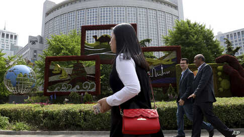 In this April 19, 2019, photo, foreigners pass by the Chinese Foreign Ministry in Beijing, China. China on Wednesday, Feb. 19,…