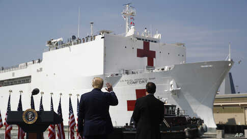 President Donald Trump waves as the U.S. Navy hospital ship USNS Comfort pulls away from the pier at Naval Station Norfolk in…