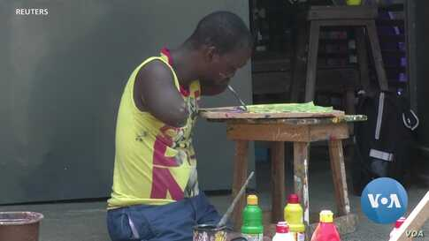 Ivorian Painter With No Arms or Legs Makes Art -- and A Living