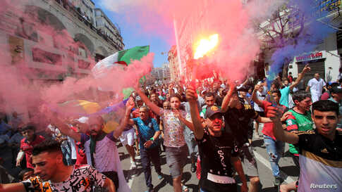 Demonstrators march during a protest demanding the removal of the ruling elite in Algiers