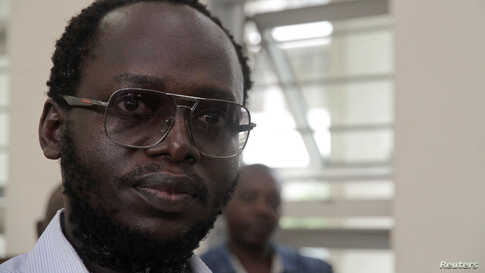 Tanzanian investigative journalist Erick Kabendera listens to his lawyers as he sits inside the Kisutu Resident Magistrate's…