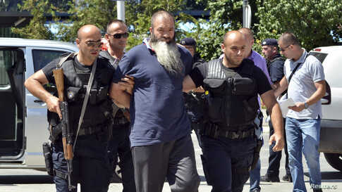Kosovo police officers escort a man (C) suspected of having fought with Islamist insurgents in Syria and Iraq as they arrive at…