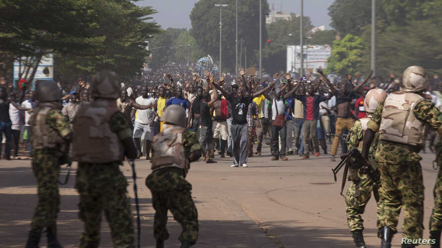 Soldiers attempt to stop anti-government protesters from entering the parliament building in Ouagadougou, capital of Burkina Faso, Oct. 30, 2014.