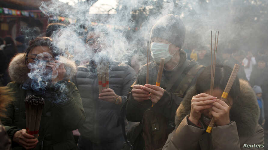 People burn incense sticks and pray for good fortune at Yonghegong Lama Temple on the first day of the Lunar New Year of the Pig in Beijing, China, Feb. 5, 2019.