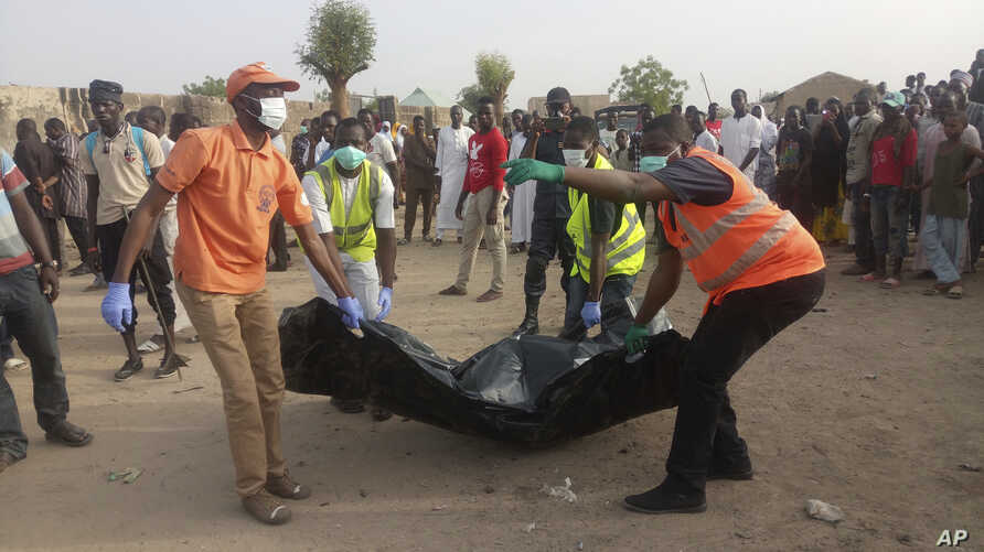 Rescue workers carry the body of a victim following a suicide attack in Maiduguri, Nigeria, April 27, 2018.